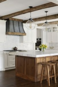 a-farmhouse-kitchen-in-neutrals-with-a-wooden-kitchen-island-and-stools-and-wooden-beams-that-cozy-up-the-space
