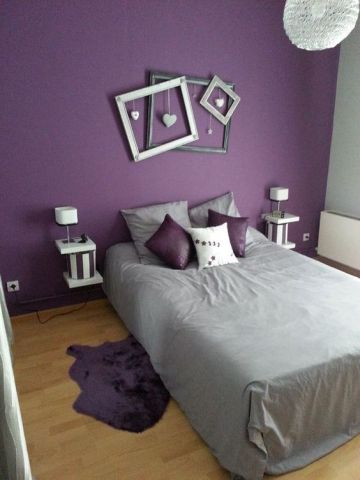 a-fun-contemporary-bedroom-with-a-purple-accent-wall-a-bed-floating-nightstands-picture-frames-and-grey-and-purple-bedding