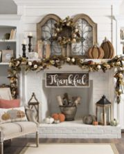 a-gorgeous-vintage-Thanksgiving-mantel-with-a-lush-dried-leaf-pumpkin-and-wheat-garland-and-wreath-wooden-pumpkins-and-candles