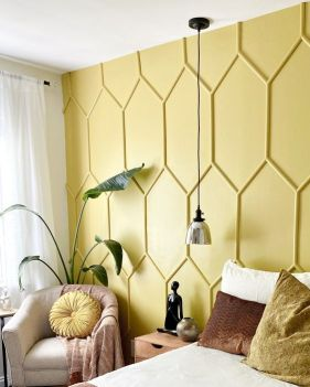 a-guest-bedroom-accented-with-a-yellow-panel-wall-with-comfy-and-chic-furniture-a-pendant-lamp-and-a-potted-plant