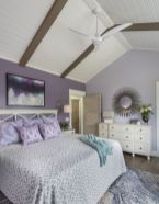 a-lavender-and-white-bedroom-with-a-purple-statement-wall-white-furniture-a-bold-artwork-a-sunburst-mirror-and-some-lavender-bedding