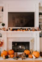 a-lovely-Thanksgiving-mantel-with-bold-leaves-candles-pinecones-small-pumpkins-on-the-mantel-and-larger-ones-next-to-the-fireplace