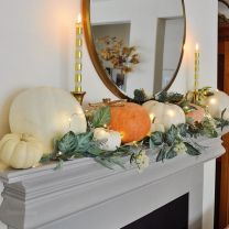 a-lovely-modern-Thanksgiving-mantel-with-greenery-white-blooms-and-large-natural-pumpkins-and-candles