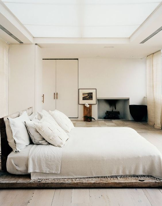a-low-key-zen-bedroom-with-a-bed-placed-on-a-wooden-platform-exquisite-furniture-and-a-built-in-fireplace-a-glazed-ceiling