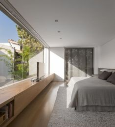 a-minimalist-bedroom-with-storage-hidden-in-the-wall-a-bed-a-sleek-storage-unit-and-a-glass-wall-with-a-view-of-a-private-courtyard