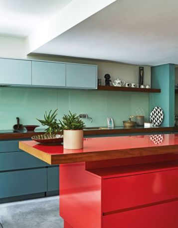 a-minimalist-kitchen-with-blue-and-muted-blue-cabinets-a-mint-green-backsplash-a-bold-red-kitchen-island-and-wooden-countertops