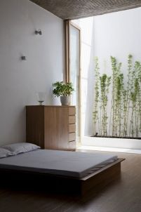 a-minimalist-zen-bedroom-with-simple-wooden-furniture-white-bedding-some-lights-connected-to-a-small-private-garden-outdoors