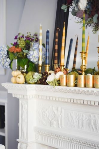 a-modern-and-bright-Thanksgiving-mantel-with-real-fresh-veggies-greenery-bold-blooms-bright-striped-candles-and-gold-candleholders