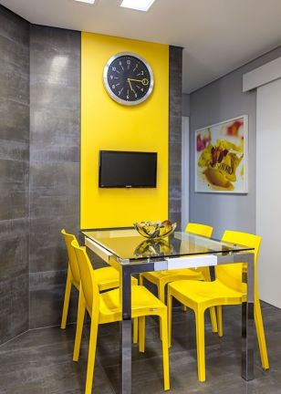 a-modern-colorful-dining-room-with-a-glass-dining-table-yellow-chairs-a-grey-wall-with-a-color-block-effect-done-with-a-yellow-panel