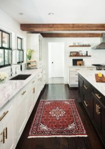 a-modern-farmhouse-kitchen-with-white-cabinets-a-black-kitchen-island-wooden-beams-a-bright-rug-and-gold-touches-is-wow