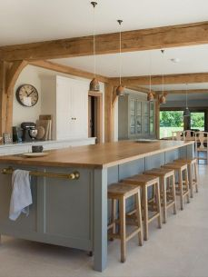 a-modern-farmhouse-kitchen-with-white-cabinets-and-a-blue-kitchen-island-wooden-beams-and-stools-pendant-lamps-for-eye-catchiness
