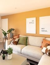 a-modern-living-room-with-yellow-walls-neutral-furniture-printed-pillows-potted-greenery-and-some-cool-prints
