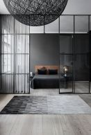 a-moody-Nordic-bedroom-with-a-black-statement-wall-a-leather-bed-nightstands-and-laps-and-a-glass-framed-wall-that-separates-it-from-the-rest-of-the-apartment