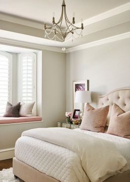 a-neutral-and-pastel-feminine-bedroom-with-an-upholstered-bed-a-crystal-chandelier-blush-and-other-pillows-and-a-metallic-nightstand