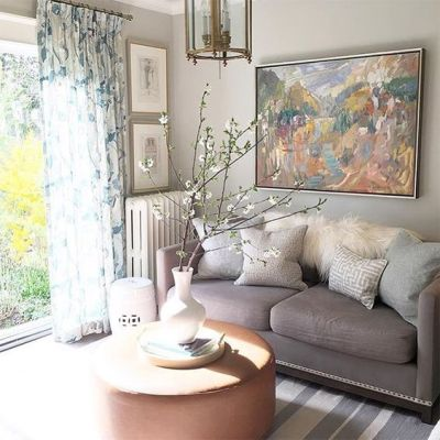 a-neutral-and-pastel-living-room-with-grey-walls-and-a-sofa-blue-touches-floral-curtains-and-a-striped-rug-plus-blooming-branches