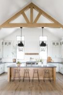 a-neutral-contemporary-kitchen-with-dark-stone-countertops-wooden-beams-a-wooden-kitchen-islnd-is-welcoming-and-stylish