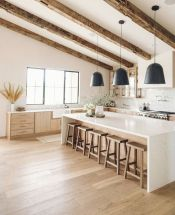 a-neutral-contemporary-kitchen-with-light-colored-cabinetry-rough-wooden-beams-with-black-pendant-lamps-is-chic-and-cozy