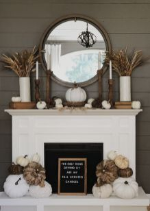 a-neutral-farmhouse-Thanksgiving-mantel-with-wheat-wooden-candleholders-some-mini-pumpkins-and-large-ones-at-the-fireplace
