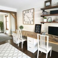 a-neutral-farmhouse-shared-home-office-with-a-pretty-wood-clad-desk-industrial-shelves-a-large-clock-and-some-white-chairs