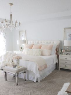 a-neutral-vintage-bedroom-with-elegant-furniture-neutral-and-pastel-textiles-a-crystal-chandelier-and-large-artworks-plus-mirror-touches