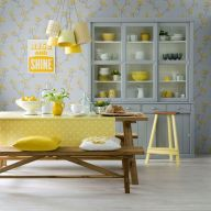a-pretty-and-cute-grey-and-yellow-dining-room-with-floral-wallpaper-a-grey-buffet-a-wooden-dining-set-pendant-lamps-and-yellow-textiles