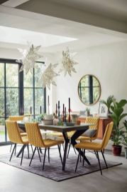a-pretty-and-whimsical-dining-room-with-a-grey-trestle-table-yellow-chairs-pillows-paper-stars-over-the-table-and-candles