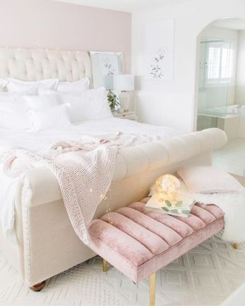 a-pretty-girlish-bedroom-done-in-white-and-light-pink-with-an-upholstered-bed-and-a-pink-bench-white-bedding-and-lights
