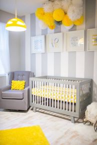 a-pretty-grey-white-and-yellow-nursery-with-a-striped-accent-wall-grey-furniture-lots-of-paper-pompoms-and-a-yellow-pendant-lamp