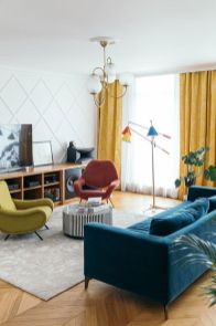 a-pretty-mid-century-modern-living-room-with-a-navy-sofa-red-and-lemon-chairs-yellow-curtains-colorful-lamps