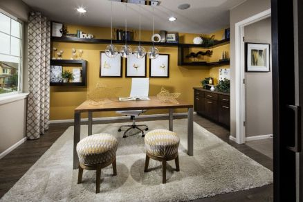 a-quirky-home-office-with-a-honey-yellow-accent-wall-and-lots-of-dark-open-shelves-a-gallery-wall-a-desk-printed-grey-and-yellow-ottomans-and-yellow-wire-fish