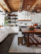 a-refined-chic-kitchen-in-white-with-stylish-cabinetry-a-wooden-table-and-benches-a-wooden-ceiling-with-beams-and-elegant-chandeliers