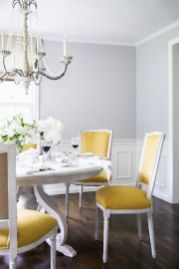 a-refined-classic-dining-room-with-grey-walls-paneling-a-large-white-table-yellow-chairs-a-beautiful-crystal-chandelier-and-white-blooms