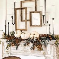 a-refined-vintage-Thanksgiving-mantel-with-lots-of-greenery-and-dried-leaves-white-pumpkins-white-candles-and-empty-frames-for-a-farmhouse-touch