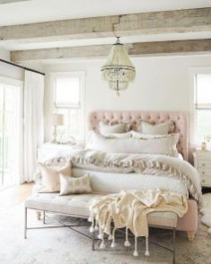a-relaxed-feminine-bedroom-with-wooden-beams-a-pink-upholstered-bed-a-leather-bench-neutral-bedding-and-a-chic-chandelier