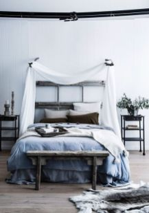 a-relaxed-zen-bedroom-with-a-reclaimed-wooden-bed-a-bench-metal-nightstands-blue-and-grey-bedding-and-a-canopy-over-the-bed