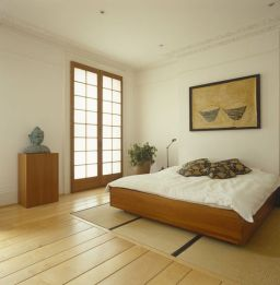 a-relaxed-zen-bedroom-with-a-wooden-bed-and-a-stand-with-a-statue-a-statement-plant-neutral-bedding-and-a-bold-artwork