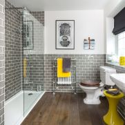 a-retro-bathroom-with-white-walls-and-grey-subway-tiles-with-white-appliances-yellow-touches-and-black-shades