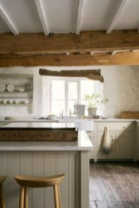 a-rustic-English-country-kitchen-in-light-grey-white-textural-walls-wooden-beams-on-the-ceiling-for-a-cozy-feel