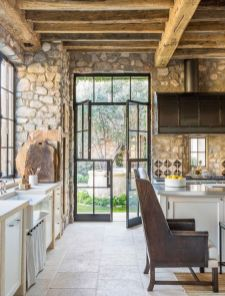 a-rustic-kitchen-with-stone-walls-wooden-beams-and-ceiling-for-much-coziness-and-white-cabinetry-plus-leather-chairs