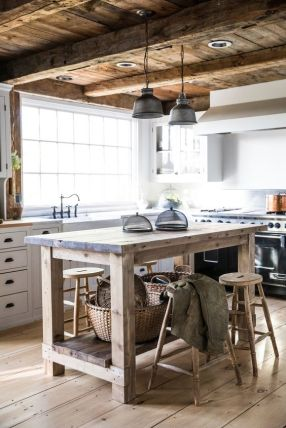 a-rustic-kitchen-with-white-cabinetry-a-rough-wooden-kitchen-island-wooden-stools-a-wooden-ceiling-and-beams-pendant-lamps-is-very-cozy
