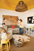 a-rustic-nursery-with-a-yellow-ceiling-grey-and-white-furniture-a-wooden-door-a-colorful-ottoman-and-yellow-touches