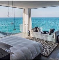 a-sea-bedroom-with-glass-walls-and-amazing-views-chic-white-furniture-pendant-lamps-and-a-pebble-rug-is-fantastic