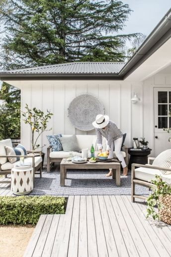 a-seaside-terrace-with-a-wooden-deck-and-light-stained-wooden-furniture-neutral-upholstery-greenery-and-a-black-and-white-decorative-plate