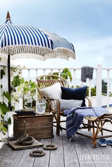 a-seaside-terrace-with-a-wooden-deck-rattan-and-wooden-furniture-bright-blue-textiles-rope-and-some-greenery