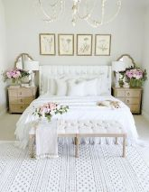 a-shabby-chic-feminine-bedroom-with-a-white-bed-and-bench-botanical-artworks-wooden-nightstands-a-chic-chandelier-and-blooms