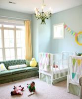 a-shared-nursery-with-light-blue-walls-a-green-sofa-white-cribs-a-colorful-banner-and-bedding-bold-yellow-touches-and-a-floral-chandelier