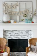 a-simple-Thanksgiving-mantel-with-oversized-white-pumpkins-bright-apples-branches-with-leaves-and-burlap-banners