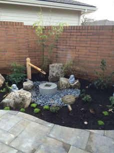 a-small-Japanese-front-yard-with-pebbles-greenery-a-stone-and-bamboo-fountain-rocks-shrubs-is-a-lovely-space