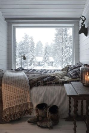 a-small-chalet-bedroom-with-a-glass-wall-a-bed-with-plaid-bedding-a-vintage-wooden-nightstand-and-a-view-of-the-forest-is-veyr-cozy