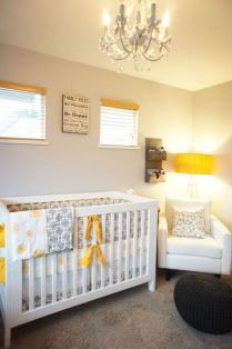 a-small-neutral-nursery-with-white-furniture-a-black-ottoman-grey-printed-textiles-and-touches-of-yellow-here-and-there